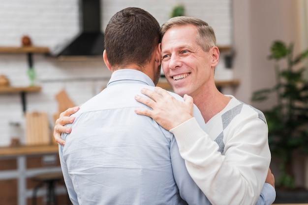Vista frontal do pai e filho abraçando Foto gratuita