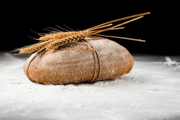 Vista frontal do pão e trigo na farinha Foto gratuita