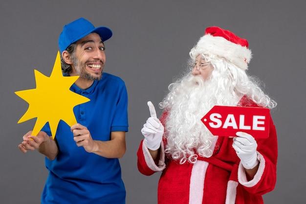 Vista frontal do papai noel com o mensageiro masculino segurando a faixa de venda e uma placa amarela na parede cinza Foto gratuita