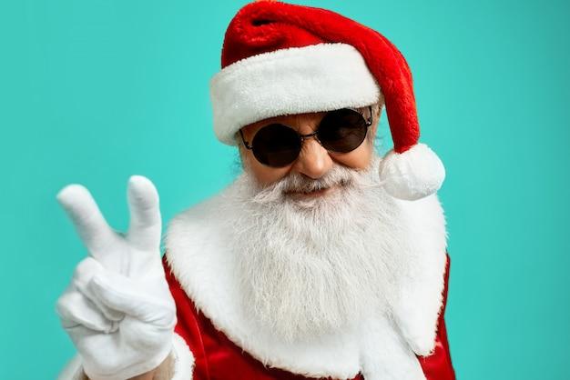 Vista frontal do papai noel sorridente com barba branca longa mostrando paz com dois dedos acima. engraçado homem elegante sênior em óculos de sol posando Foto gratuita