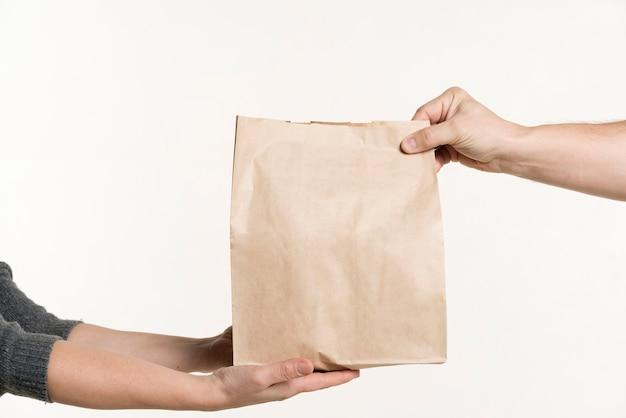 Vista frontal do par de mãos segurando um saco de papel Foto Premium