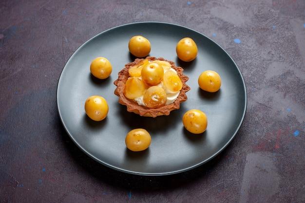 Vista frontal do pequeno bolo cremoso com cerejas frescas dentro do prato na superfície escura Foto gratuita