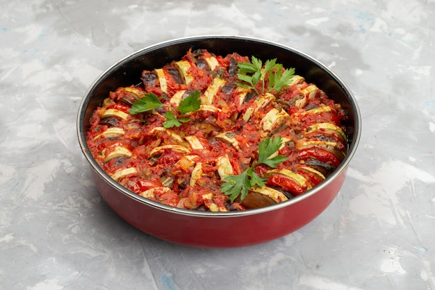 Vista frontal do prato de legumes cozidos dentro da panela na mesa brilhante Foto gratuita