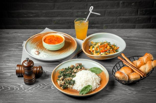 Vista frontal do primeiro segundo e prato principal sopa de lentilha salada de legumes e arroz com carne e suco em cima da mesa Foto gratuita