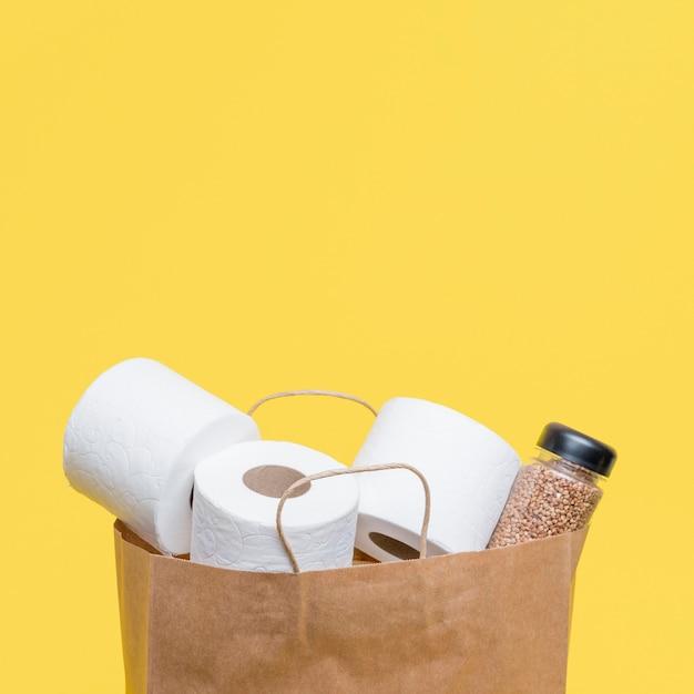 Vista frontal do saco de papel com rolos de papel higiênico e espaço para texto Foto gratuita