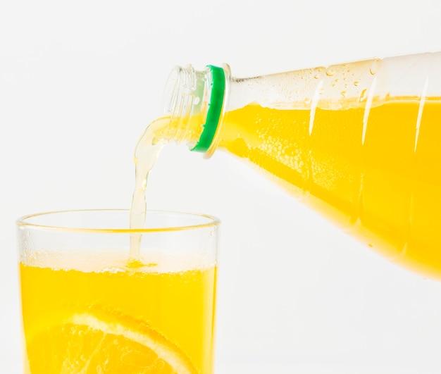 Vista frontal do suco de laranja sendo servido no copo da garrafa Foto gratuita