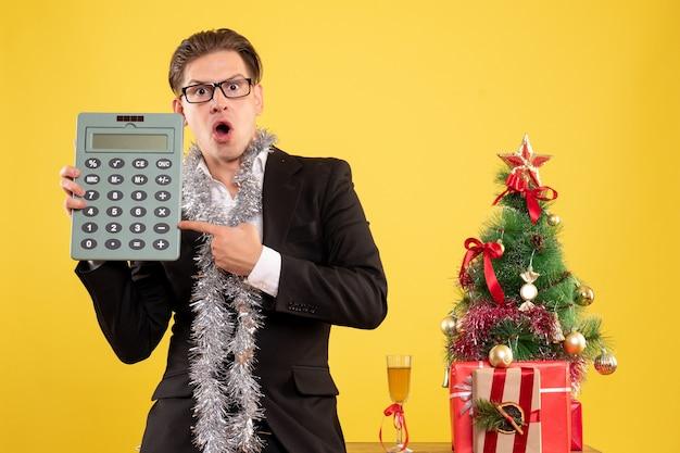 Vista frontal do trabalhador masculino em pé e segurando calculadora Foto gratuita