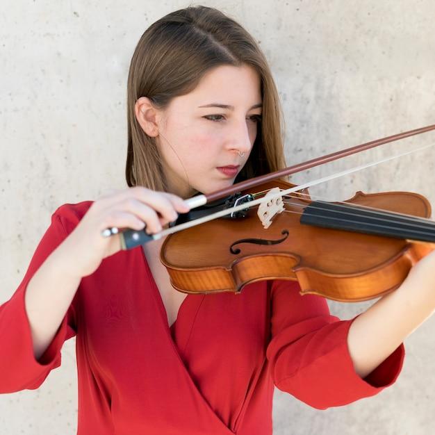 Vista frontal do violinista feminino tocando Foto gratuita