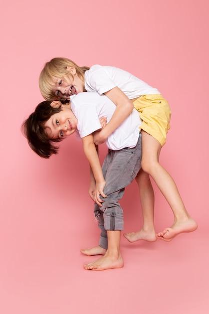 Vista frontal, dois meninos brincando uns com os outros em camiseta branca na mesa-de-rosa Foto gratuita