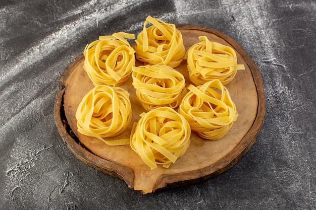 Vista frontal em forma de massa italiana em forma de flor crua e amarela em mesa de madeira marrom Foto gratuita
