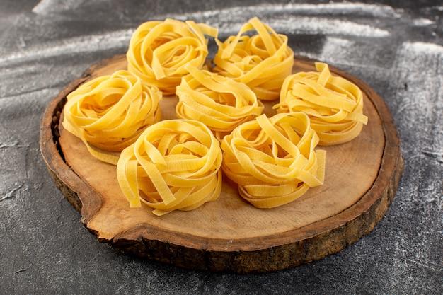 Vista frontal em forma de massa italiana em forma de flor crua e amarela sobre marrom Foto gratuita