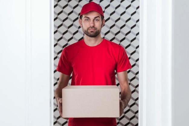 Vista frontal entrega homem vestindo uniforme vermelho Foto gratuita