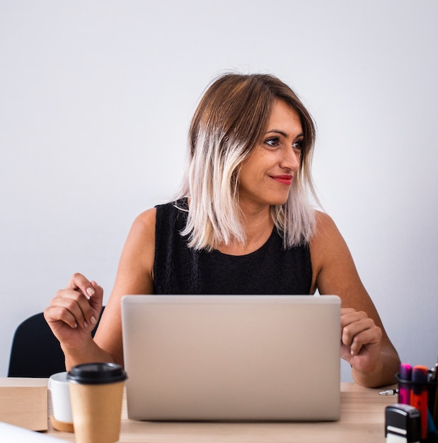 Vista frontal feminina no trabalho usando laptop Foto gratuita