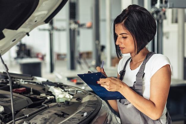 Vista frontal feminino mecânico inspecionando carro Foto gratuita