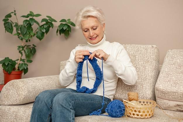 Vista frontal feminino sênior no sofá de tricô Foto gratuita