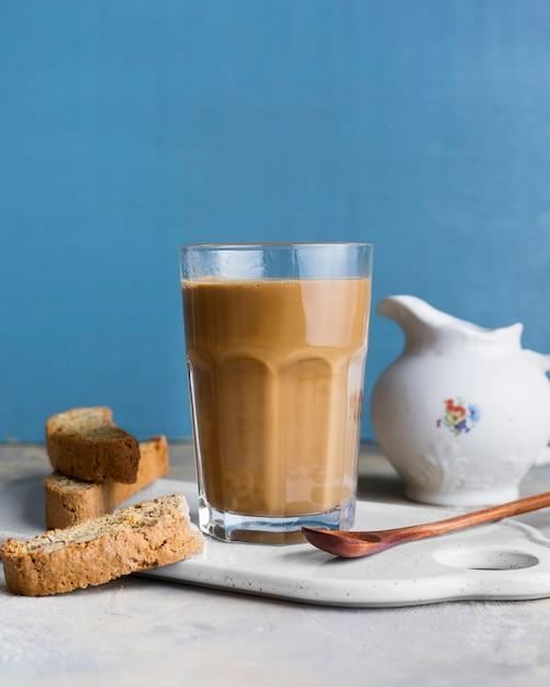 Vista frontal frappe no copo ao lado de fatias de pão com sementes Foto Premium