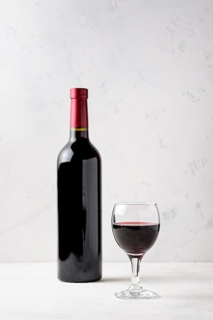 Vista frontal garrafa de vinho tinto ao lado de vidro Foto Premium