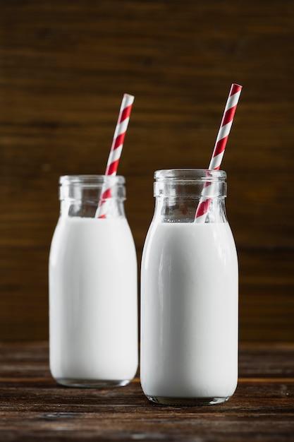 Vista frontal garrafas de leite com canudos Foto gratuita