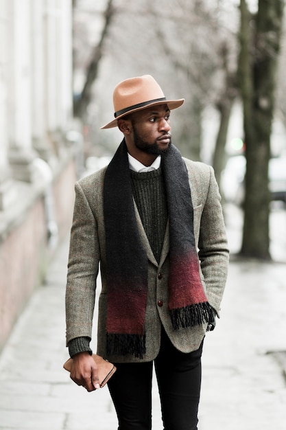 Vista frontal homem bonito casaco cinza andando lá fora Foto gratuita