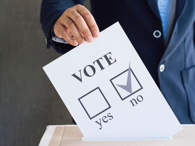 Vista frontal homem colocando sua cédula de referendo em uma caixa Foto gratuita