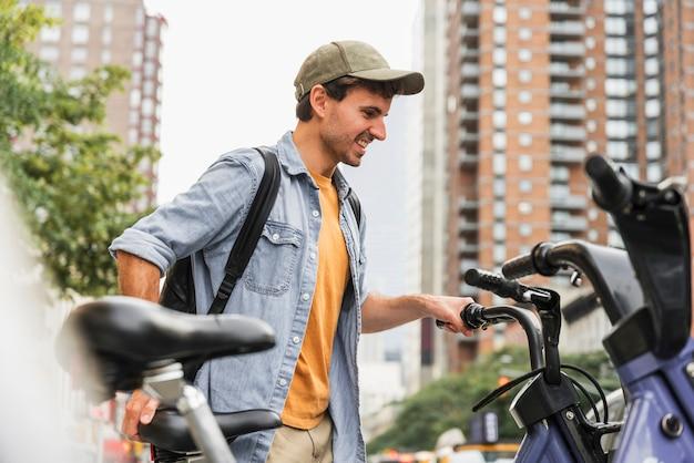 Vista frontal homem com bicicleta na cidade Foto gratuita
