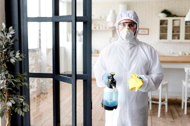 Vista frontal homem com garrafa de desinfecção Foto Premium