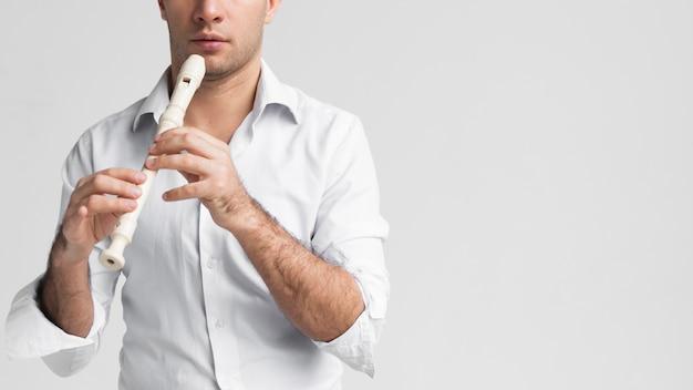 Vista frontal homem de camisa branca tocando flauta Foto gratuita