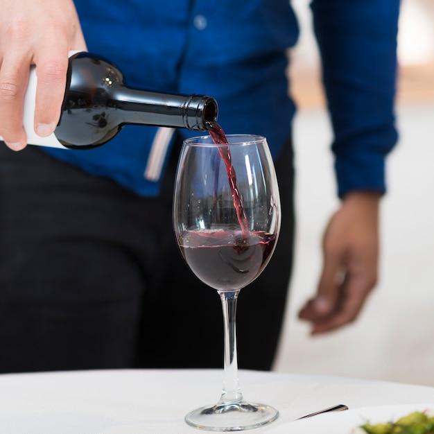 Vista frontal homem derramando vinho em um copo para sua esposa, close-up Foto gratuita