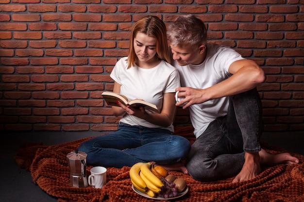 Vista frontal homem e mulher lendo juntos um livro Foto gratuita