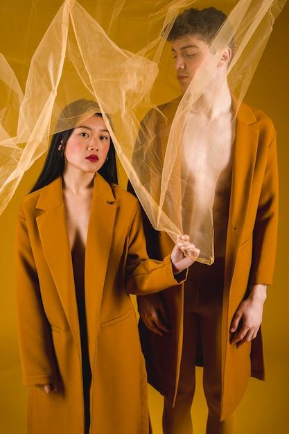 Vista frontal homem e mulher posando com um tecido transparente Foto gratuita
