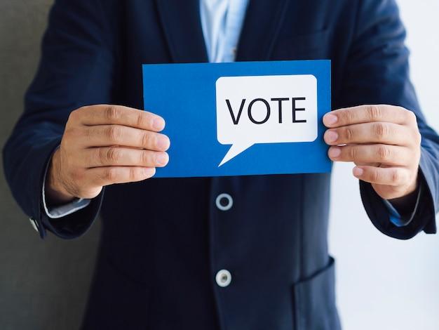 Vista frontal homem mostrando um cartão de voto com uma bolha do discurso Foto gratuita