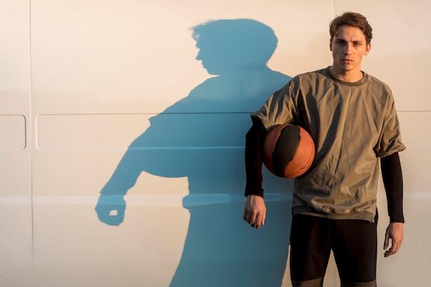 Vista frontal homem posando com uma bola de basquete Foto gratuita