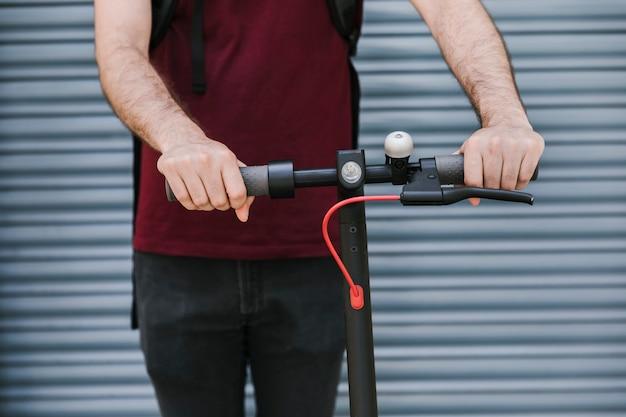 Vista frontal homem segurando alças de e-scooter Foto gratuita