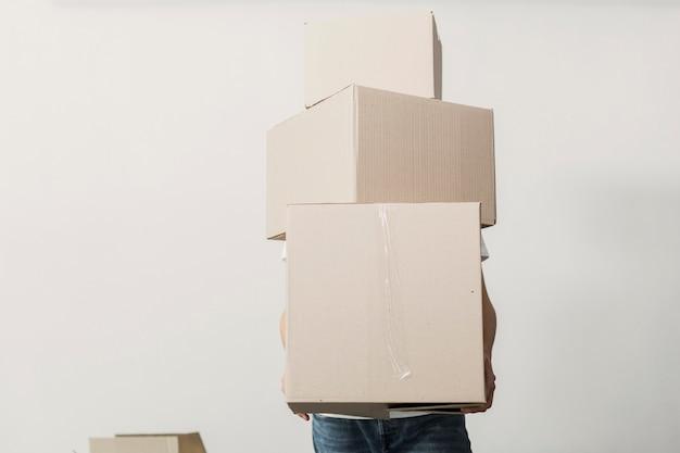 Vista frontal homem segurando caixas de papelão Foto gratuita