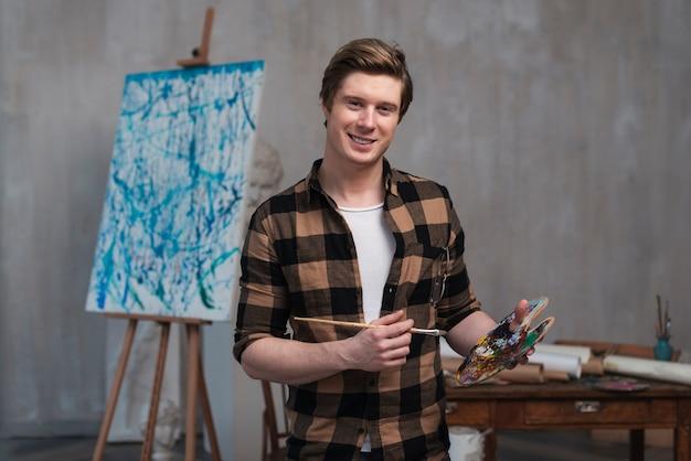Vista frontal homem sorridente mistura cores diferentes para sua pintura Foto gratuita