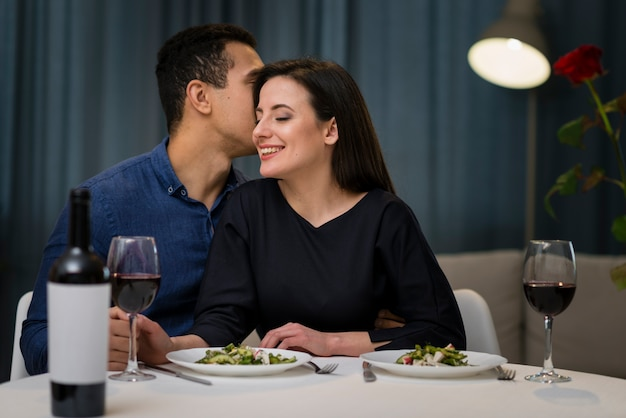 Vista frontal homem sussurrando algo para sua namorada Foto gratuita