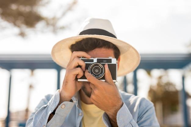 Vista frontal homem tirando fotos Foto gratuita