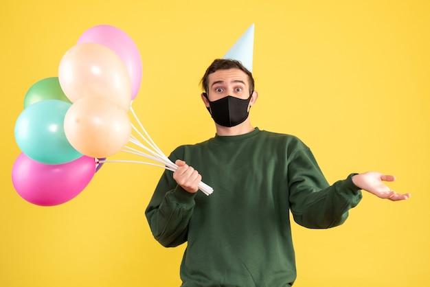 Vista frontal imaginou jovem com boné de festa e balões coloridos em pé sobre amarelo Foto gratuita