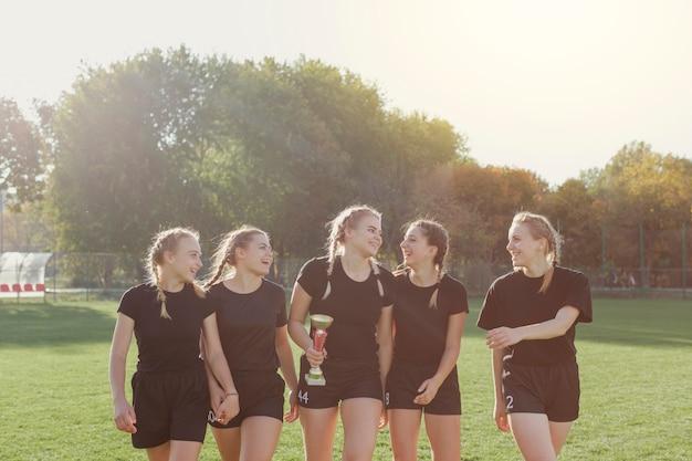Vista frontal jogadores de futebol feminino, segurando um troféu Foto gratuita