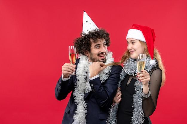 Vista frontal jovem casal comemorando ano novo no feriado de parede vermelha adora festa de natal Foto gratuita