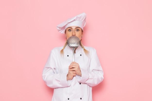 Vista frontal jovem cozinheira em terno branco, posando com uma colher de prata no espaço rosa. Foto gratuita