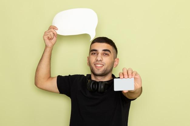 Vista frontal jovem do sexo masculino com camiseta preta segurando uma placa branca e um cartão verde Foto gratuita