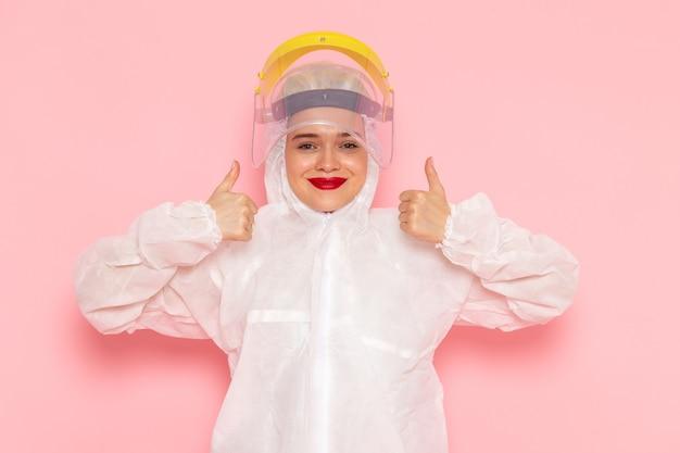Vista frontal, jovem e linda mulher em um terno branco especial usando um capacete amarelo especial, mostrando como um sinal no espaço rosa mulher com terno especial Foto gratuita