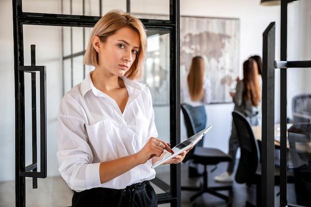 Vista frontal jovem fêmea no escritório trabalhando em tablet Foto gratuita