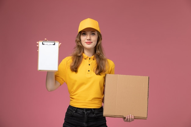 Vista frontal jovem mensageira de uniforme amarelo segurando a caixa de comida com o bloco de notas no fundo rosa escuro uniforme entrega trabalho serviço trabalhador Foto gratuita