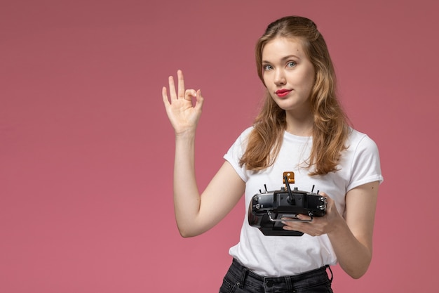 Vista frontal jovem mulher atraente em camiseta branca posando segurando o controle remoto na parede rosa cor do modelo feminino jovem Foto gratuita