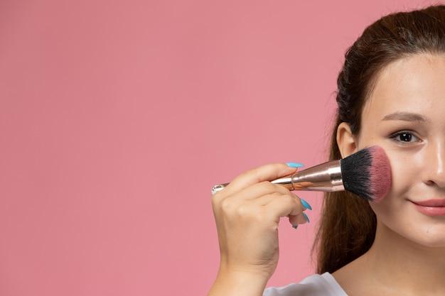 Vista frontal jovem mulher atraente em smi de camiseta branca e fazendo maquiagem no fundo rosa Foto gratuita