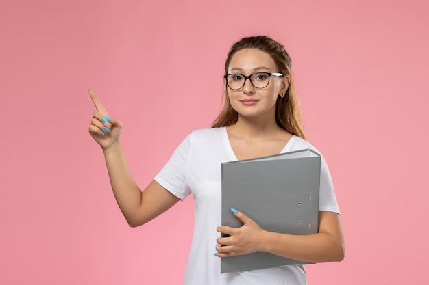 Vista frontal, jovem mulher atraente em uma camiseta branca segurando um documento cinza no fundo rosa Foto gratuita