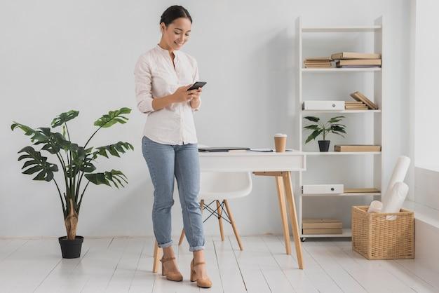 Vista frontal jovem no escritório usando móveis Foto gratuita