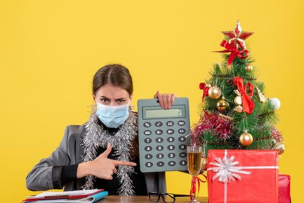 Vista frontal jovem séria com máscara médica sentada à mesa apontada com calculadora de dedo árvore de natal e coquetel de presentes Foto gratuita